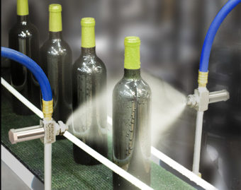 2 dysze rozpylające z mieszaniem zewnętrznym o szerokokątnym strumieniu płaskim są używane do końcowego płukania dezynfekującego przed etykietowaniem butelek wina.
