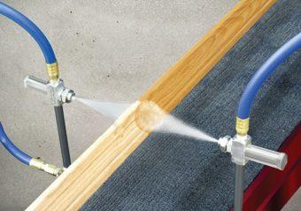 2 dysze rozpylające są używane do nakładania powłoki ogniochronnej na listwę drewnianą.